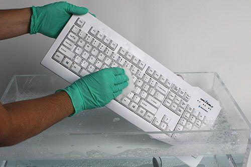 wit waterdicht toetsenbord van seal shield dat gewassen wordt in een bak met water dit terwijl het vast gehouden wordt door twee handen