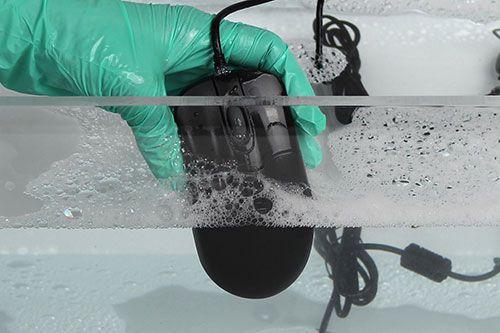 zwarte seal shield muis die wordt gewassen in een bak met water en sop dit terwijl een hand met handschoen hem vasthoudt