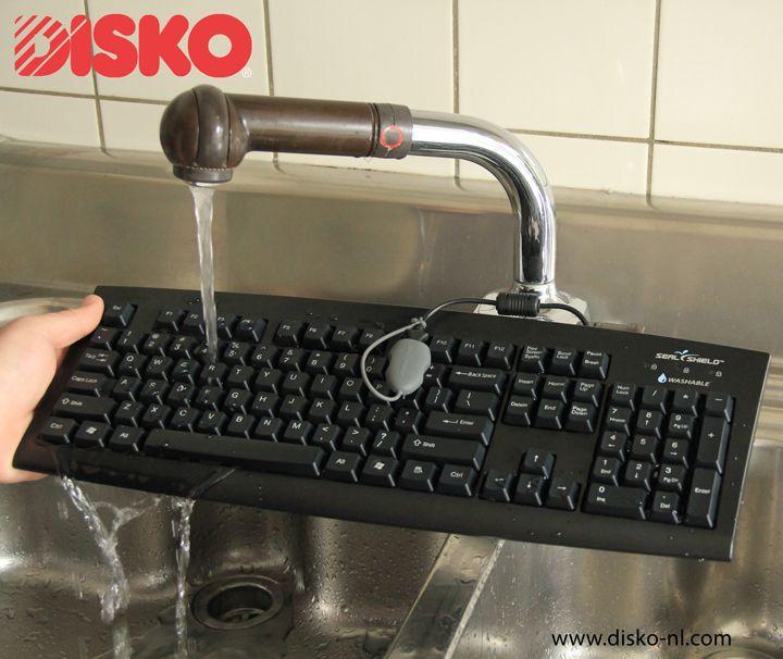 waterdicht toetsenbord zwart van het merk seal shield toetsenbord wordt onder de stromende kraan gehouden om de waterdichtheid te demonstreren