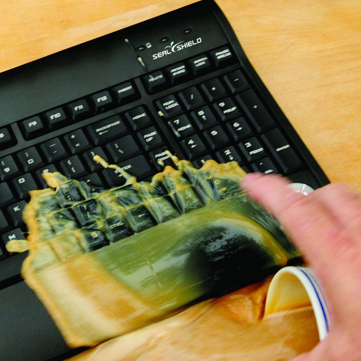 waterdicht toetsenbord zwart van het merk seal shield op de foto wordt een kopje koffie over het toetsenbord heen gegooid